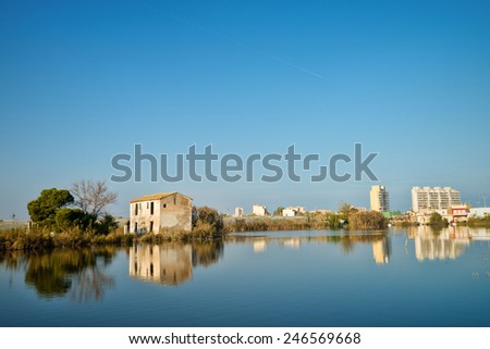 Old farmhouses and modern hotels in Albufera natural reserve, Valencia, Spain - stock photo