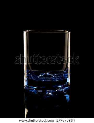 Old fashined glass in the low-key lighting and surface reflection - stock photo