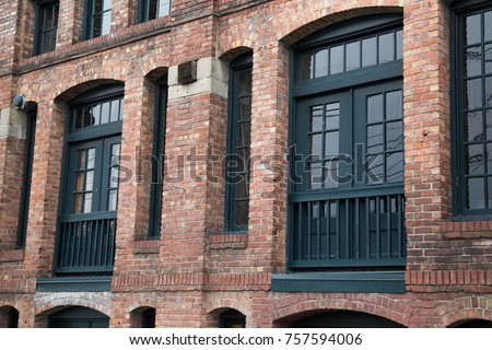 Old Fashion Brick Apartment And Loft Building With Red Masonry Pillars Arches Over Green