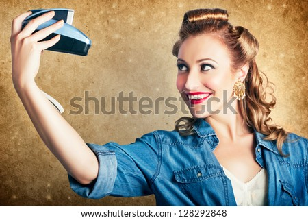 Old Fashion Female Photographer With Fifties Style Hair Rolls Taking Self Portrait With A Vintage Camera In A Depiction Of A Selfie - stock photo