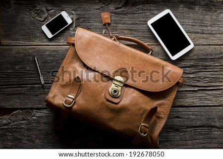 Old fashion leather briefcase shot with Smart-phone and computer tablet - stock photo