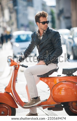 old fashionable man riding  a vintage scooter in the street, he wears a leather jacket - stock photo
