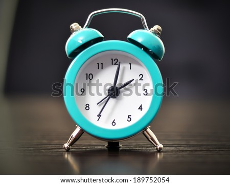 Old fashioned alarm clock on table, close up - stock photo