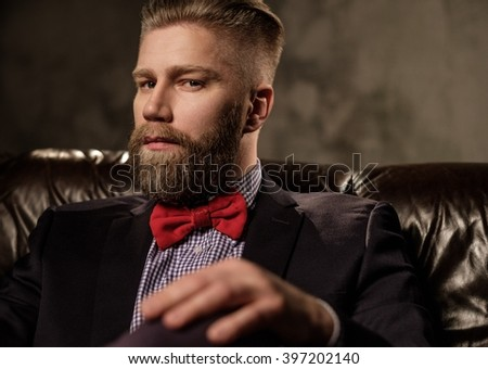 Old-fashioned bearded man sitting in comfortable leather sofa