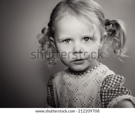 Old-fashioned black and white portrait of pretty little girl with serious look in her eyes. Shallow DOF and sepia toned hues. - stock photo