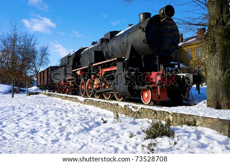 Old fashioned black - red locomotive as a monument