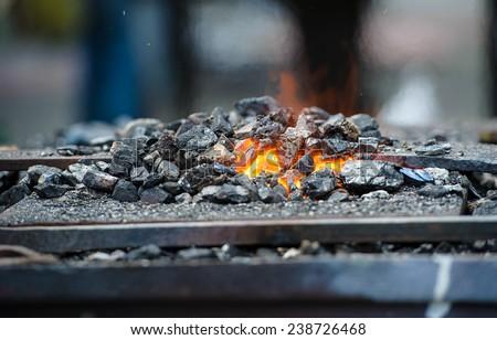 Old fashioned blacksmith furnace with burning coals - stock photo