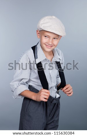 Old fashioned boy and looking sideways on gray background. Closeup. - stock photo