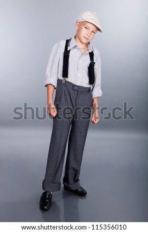 Old fashioned boy and looking to the camera on gray background - stock photo