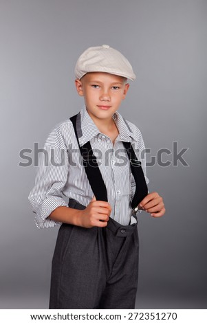 Old fashioned boy looking to the camera on gray background - stock photo
