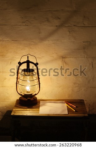 Old fashioned burning kerosene lantern, a blank sheet of paper and two pencils on the old wooden table near old brick wall in the darkness - stock photo