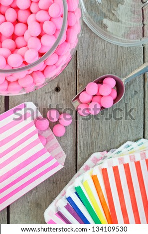 Old fashioned candy jar full of pink peppermints being distributed into individual candy bags. - stock photo