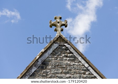 Old fashioned carved stone cross set on roof of religious building in Wales, England. - stock photo