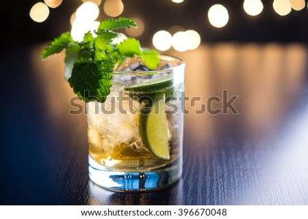 Old fashioned cocktail with lime and mint on the wooden table. Shallow depth of field. - stock photo