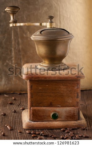 old-fashioned coffee grinder and roasted coffee beans on brown wooden table