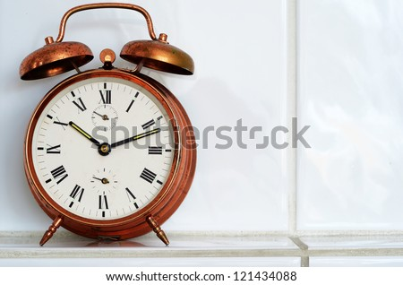 old-fashioned copper alarm clock on the mantelshelf - stock photo