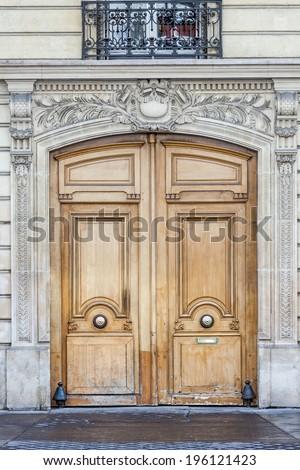 Old fashioned front door entrance, grey facade and brown door, Paris