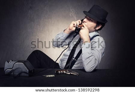 old fashioned gangster having a conversation on phone on grunge background - stock photo