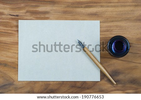 old fashioned ink dip pen for writing or drawing on wooden table with parchment paper background