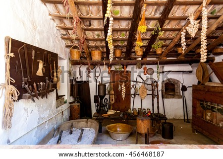 Old-fashioned kitchen with ancient dishes and hanging garlic and onion