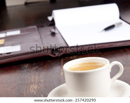 Old fashioned leather folder with blank paper and a cup of coffee - stock photo