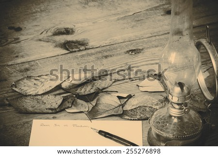 Old fashioned letter with a lamp and leafs - stock photo