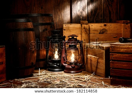 Old fashioned light kerosene lantern style oil lamps in antique shipping warehouse stockroom with vintage wooden crates containers and ancient storage boxes near retro whiskey transportation barrels - stock photo