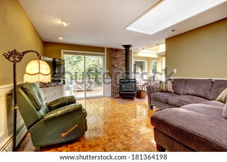 Old fashioned living room with green wall and brick trim.  View of the antique stove, leather armchair and sofa. - stock photo