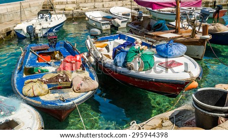 Old-fashioned mediterranean fishing boats with colorful bags and nets moored. Petrovac marina, Montenegro - stock photo
