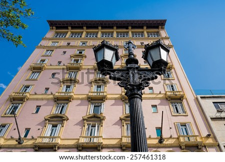 Old-fashioned metal street lamp and apartment building - stock photo