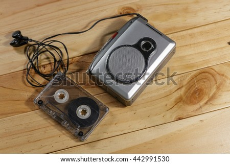 old-fashioned music cassette with earphones, vintage audio cassette on wooden background