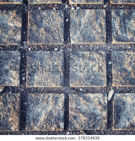 Old fashioned pavement. Stone roadway. Square pattern. Aged photo. Abstract background. Pavement tiles in gray stone. - stock photo