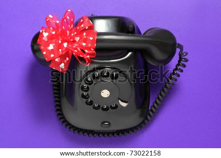 Old-fashioned phone isolated on a purple background with red ribbon with white hearts. - stock photo