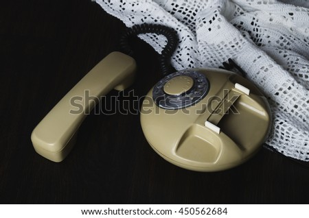 old-fashioned phone on knitted napkin on a dark wooden table. top view, horizontal format - stock photo