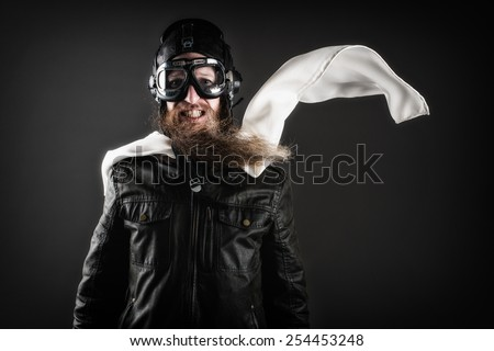 Old fashioned pilot with goggles and a scarf - stock photo