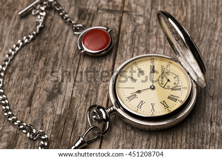 Old fashioned pocket watch with chain on rough wood  - stock photo