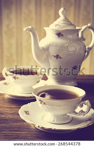 Old-fashioned porcelain kettle with two cups of tea with vintage style - stock photo