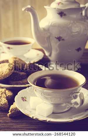 Old-fashioned porcelain two cups of tea with cookies in vintage style with cookies - stock photo