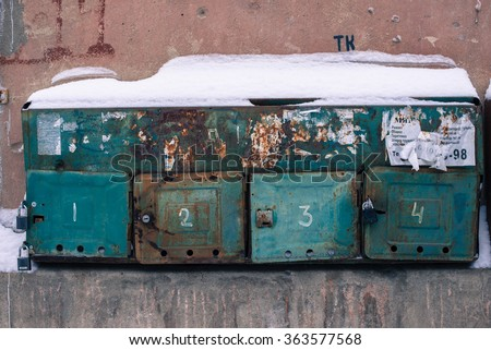 Old-fashioned shabby rusty mailboxes on the house wall in Russia, numbers 1,2,3,4 - stock photo