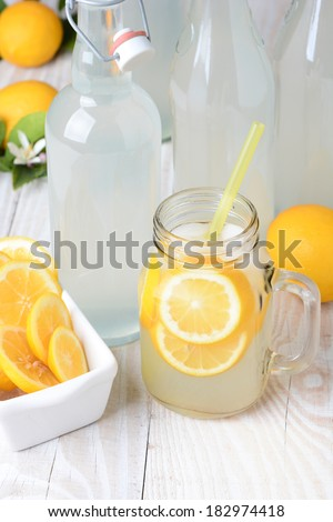 Old fashioned sparkling lemonade shot from a high angle. Vertical format on a rustic wooden farmhouse style table. - stock photo