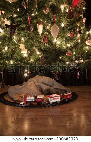 old fashioned steam locomotive beneath a decorated christmas tree, vintage feel  - stock photo