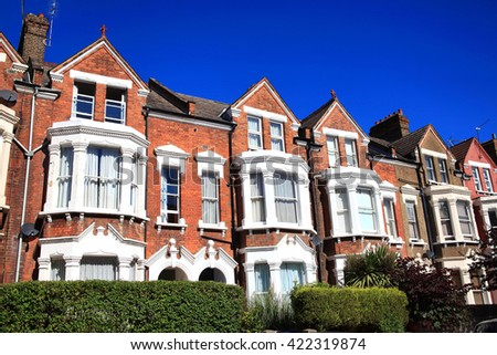 Old fashioned typical Victorian terraced town houses architecture in London, England, UK. These residential homes are often turned into apartment flats - stock photo