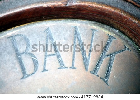 Old fashioned vintage bank sign above its building entrance - stock photo
