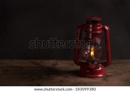 Old fashioned vintage kerosene oil lantern lamp burning with a soft glow light with aged wooden floor