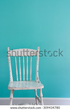 Old-fashioned white chair in front of a wall. Natural light from the window. - stock photo