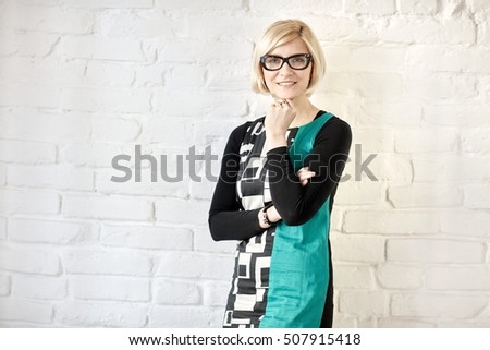 Old-fashioned woman standing front of white brick wall, smiling, looking at camera.