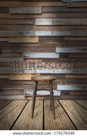 Old-fashioned wooden round chair on old plank of wood floor and old wooden wall - stock photo
