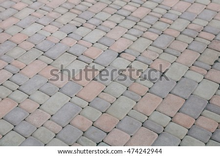 Old fasion light, dark grey and red paving slabs laid out on different size cubes