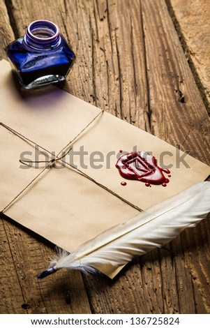 Old feather, envelope, sealing wax and ink bottle - stock photo