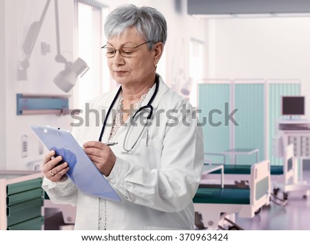 Old female doctor writing notes on clipboard at hospital room, - stock photo